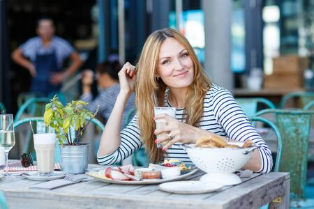 cafe: Happy beautiful woman drinking coffee with milk and having healthy breakfast in outdoor cafe in summer city in Europe. Stock Photo