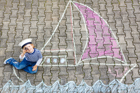 chalk drawing: Adorable little kid boy playing with colorful chalks and painting ship or boat picture. Creative leisure for children outdoors in summer