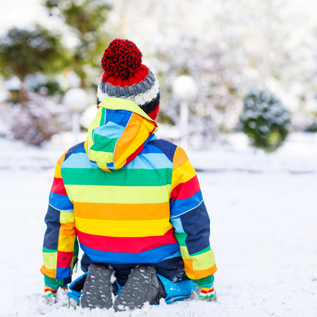 outoors: Portrait of little child in colorful clothes in winter from the back, outdoors  on cold day. Active outoors leisure with children in winter.