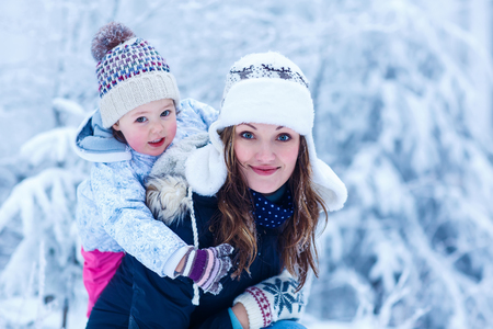 family portrait: portrait of a little girl and her young beautiful mother in winter hat in snow forest at snowflakes background. outdoors winter leisure and lifestyle with kids on cold days