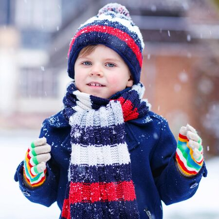 outoors: Portrait of little funny boy in colorful winter clothes having fun with snow, outdoors during snowfall. Active outoors leisure with children in winter. Kid with warm hat, hand gloves and scarf with stripes. Happiness about snow.