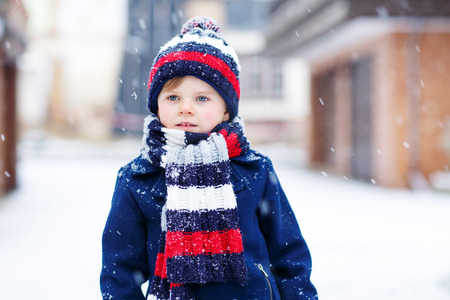 Portrait of beautiful toddler child, boy, in winter clothes with stripes, outdoors, during snowfall on cold day. Active outoors leisure with kids in winter.