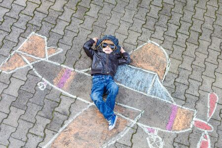 Funny little kid boy flying by a plane picture painting with colorful chalk. Creative leisure for children outdoors in summer.