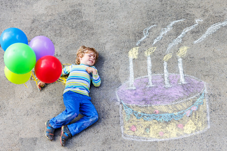 leisure: Happy little kid boy having fun with big birthday cake picture drawing with colorful chalks and balloons. Creative leisure for children outdoors in summer. Stock Photo