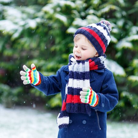 having fun in the snow: Active little kid boy in colorful winter clothes having fun with snow, catching snowflakes, outdoors during snowfall on cold day. Active outoors leisure with children in winter.