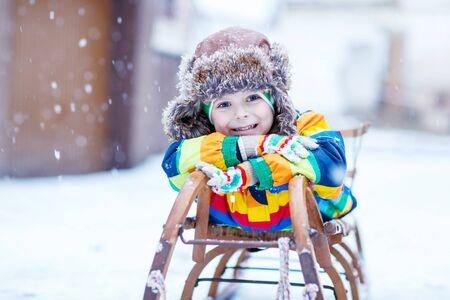 snow day: Cute little funny boy in colorful winter clothes sliding on snow sledge, outdoors during snowfall. Active outoors leisure with children in winter. Kid with warm hat, hand gloves and scarf with stripes. Happiness about snow.