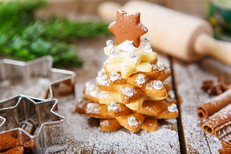 Homemade baked Christmas gingerbread tree on vintage wooden . Anise, cinnamon, baking roll, star forms and decoration utensils. With icing sugar snow. Selfmade gift for xmas. Standard-Bild