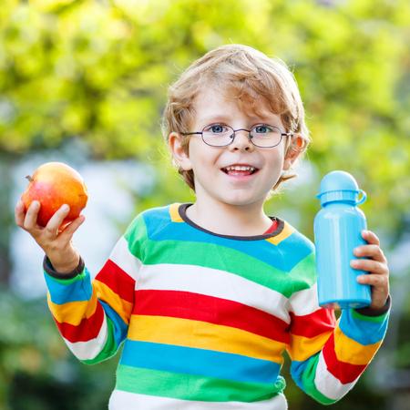carita feliz: Ni�o peque�o divertido con la manzana y la botella de la bebida en su primer d�a a la escuela primaria o en la guarder�a. Al aire libre. Volver a la escuela, los ni�os, el concepto de estilo de vida