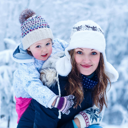 portrait of a little girl and her young beautiful mother in winter hat in snow forest at snowflakes . outdoors winter leisure and lifestyle with kids on cold days