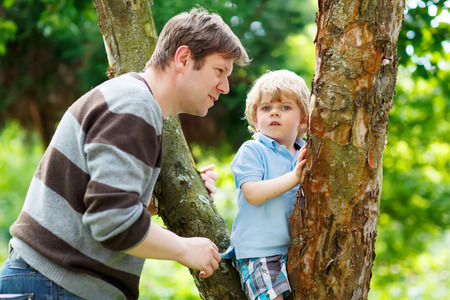 leisure equipment: Man and his adorable little child having fun in forest. Funny kid boy climbing on tree. Family leisure outdoors, on warm summer day.