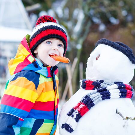 having fun in the snow: Funny little kid boy making a snowman and eating carrot, playing and having fun with snow, outdoors  on cold day. Active outoors leisure with children in winter. Stock Photo