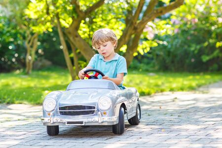 alone boy: Little preschool boy driving big toy old vintage car and having fun, outdoors. Active leisure with kids on warm summer day.