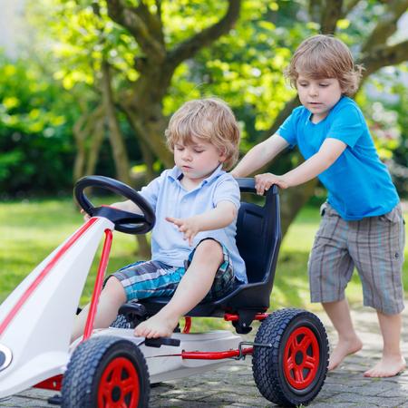 niño empujando: Dos niño pequeño y de hermanos varones activos felices en divertirse con el coche de carreras de juguete en el jardín de verano, al aire libre. Hermano adorable que empuja el coche con el niño más joven. Juegos al aire libre para los niños en verano concepto.