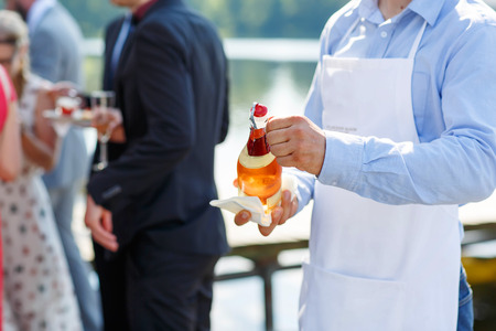 cheer full: Waiter with bottle of champagne. On outdoor wedding reception in summer.