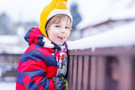 outoors: Little kid boy eating and tasting snow, outdoors  on cold day. Active outoors leisure with children in winter.