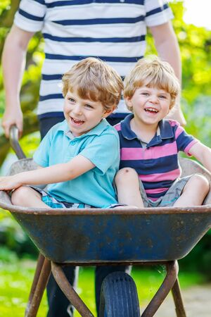 domestic garden: Two blond little boys having fun in a wheelbarrow pushing by father in domestic garden, on warm sunny day. Active outdoors games for kids in summer. Stock Photo