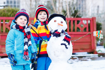 outoors: Two little friends making a snowman, playing and having fun with snow, outdoors  on cold day. Active outoors leisure with children in winter. Stock Photo