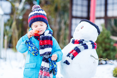 Happy little toddler boy making a snowman and eating carrot, playing and having fun with snow, outdoors  on cold day. Active outoors leisure with kids in winter.