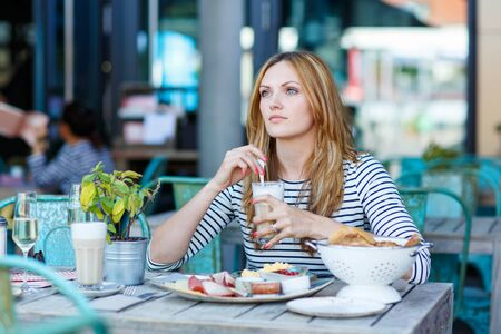 bistro cafe: Young beautiful woman drinking coffee with milk and having healthy breakfast in outdoor cafe in summer city in Europe.