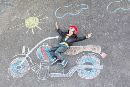 leisure: Creative leisure for children: Happy little child of four years in helmet having fun with motorcycle picture drawing with colorful chalks. Children, lifestyle, fun concept.
