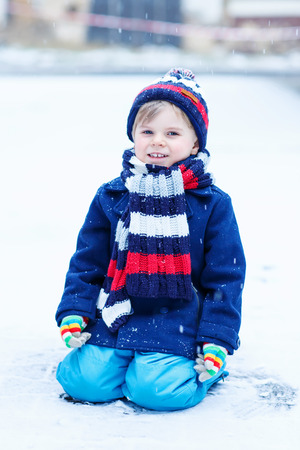 outoors: Cute little funny kid boy in colorful winter clothes sitting on snow, outdoors during snowfall on cold day. Active outoors leisure with children in winter.