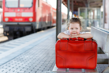 suitcase: Cute little girl with big red suitcase on a railway station. Kid waiting for train and happy about a journey. Stock Photo
