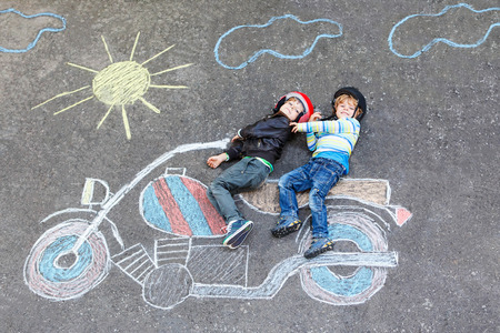 a picture: Creative leisure for children: two little funny friends in helmet having fun with motorcycle picture drawing with colorful chalks. Children, lifestyle, fun concept. Stock Photo