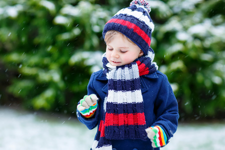 outoors: Cute little funny child in colorful winter clothes having fun with snow, outdoors during snowfall on cold day. Active outoors leisure with children in winter.