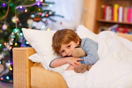 christmas toy: Cute little blond boy in his bed near Christmas tree with lights holding teddy bear toy. Tired child dreaming and relaxing. Stock Photo