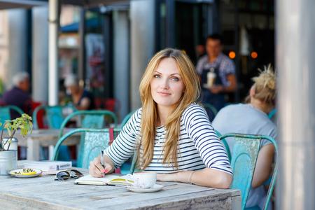 persona escribiendo: Joven y bella mujer bebiendo café y escribiendo el diario, libro o notas en un café al aire libre en París, Francia. Foto de archivo