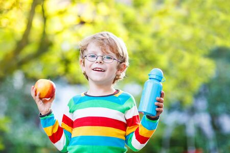 Beatiful little kid boy with  apple and drink bottle on his first day to elementary school or nursery. Outdoors.  Back to school, kids, lifestyle concept