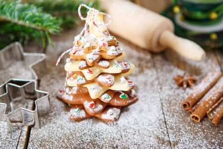als: Homemade baked Christmas gingerbread tree on vintage wooden . Anise, cinnamon, baking roll, star forms and decoration utensils. With icing sugar als snow. Selfmade gift for xmas.