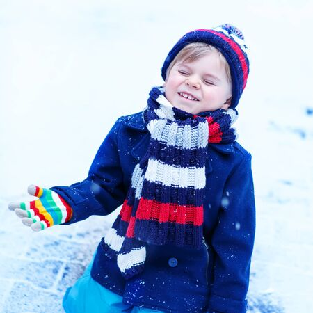 having fun in the snow: Funny and happy toddler boy in colorful winter clothes having fun with snow, outdoors during snowfall. Active outoors leisure with children in winter. Kid with warm hat, hand gloves and scarf with stripes. Happiness about snow.