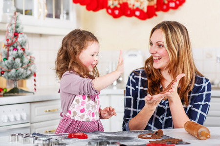 Happy mother, young woman in red santa hat baking christmas cookies together with her little daughter, cute blonde kid girl, sitting at the table in domestic kitchen Stok Fotoğraf