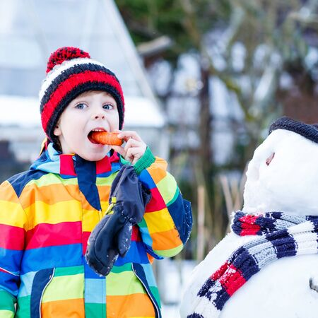 having fun in the snow: Funny little child making a snowman and eating carrot, playing and having fun with snow, outdoors  on cold day. Active outoors leisure with kids in winter. Stock Photo