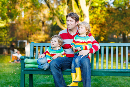 kiddies: Young man and his two little blond sons sitting together in colorful clothing. Happy kid boys and their dad having fun in autumn park on warm day. Stock Photo