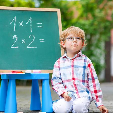 pizarron: Hermoso ni�o peque�o ni�o con gafas en la pizarra pensando en matem�ticas, al aire libre. la escuela o guarder�a. Volver al concepto de escuela