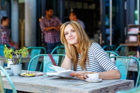독일 함부르크에있는 야외 카페에서 젊은 아름 다운 여자 마시는 커피와 책을 읽고.