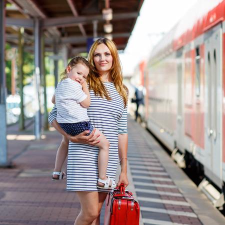 tren: mujer joven y su pequeña hija en una estación de ferrocarril. Muchacha del cabrito y la madre en espera de tren y feliz por un viaje. La gente, los viajes, la familia, el estilo de vida concepto Foto de archivo
