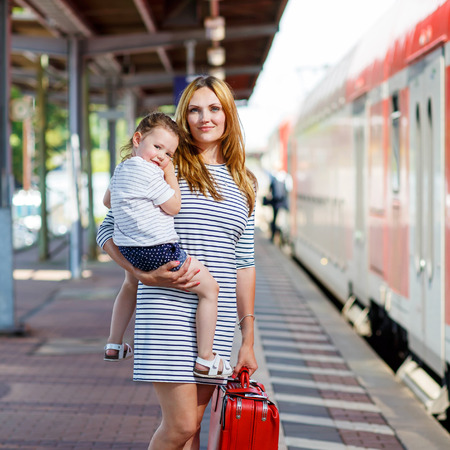 baggage train: young woman and her little daughter on a railway station. Kid girl and mother waiting for train and happy about a journey. People, travel, family, lifestyle concept