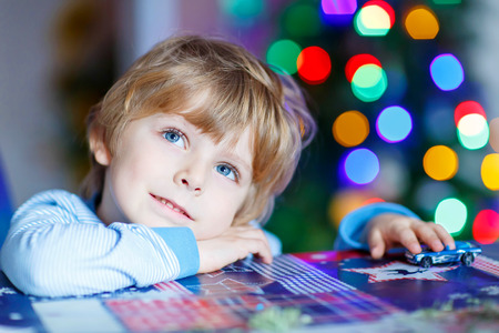 Little blond child playing with cars and toys at home, indoor. Cute happy funny boy having fun with gifts. Colorful christmas lights on background. Family, holiday, kids lifestyle conceplt.
