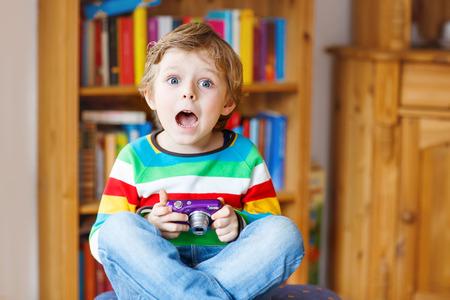 niños rubios: Activo muchacho niño que se divierte con la fabricación de fotos con photocamera, en interiores. Niño vestido con camisa colorida. Retrato en una guardería.