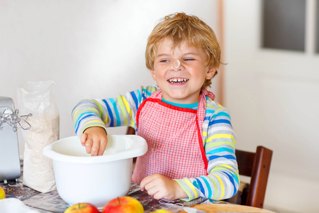 cake mixer: Cute happy blond kid boy baking apple cake in domestic kitchen. Child having fun with working with mixer, dough, eggs and fruits. With flour on nose