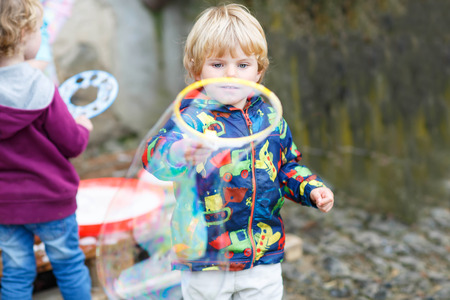 three years old: Three years old caucasian child boy blowing soap bubbles outdoor on birthday party - happy carefree childhood. Kid having fun.