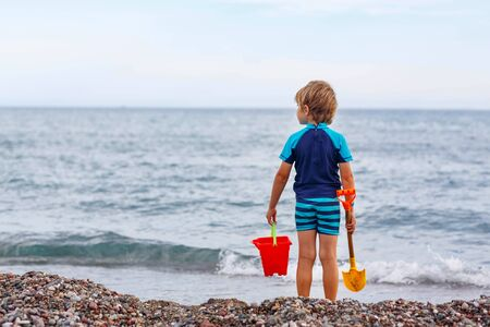 signe de la main: Adorable little blond kid boy standing on lonely ocean beach. Child playing and looking on horizon. Vacations, summer, travel concept. Preschool boy enjoying summer vacations on sea.