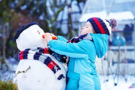 bonhomme de neige: Adorable enfant gar�on faisant un bonhomme de neige et de manger la carotte, jouer et avoir du plaisir avec de la neige, � l'ext�rieur le jour froid. Ext�rieur loisir actif avec les enfants en hiver. Banque d'images