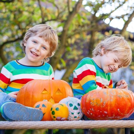 Two little kids making jack-o-lantern for halloween in autumn garden, outdoors. Happy family having fun together