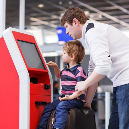 checking in: Happy family of two: Father and little son at the international airport, traveling together and checking in at terminal. Stock Photo