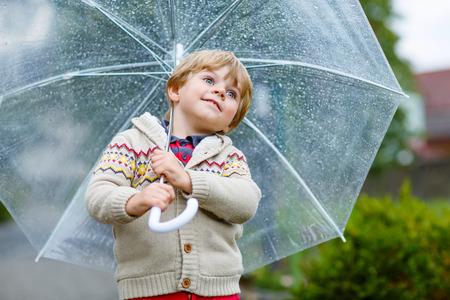 rain boots: Ni�o peque�o ni�o rubio caminando con el paraguas grande al aire libre en d�a de lluvia. Ni�o que se divierte y con ropa de colores impermeables y botas de lluvia.