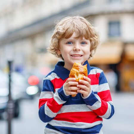 eating pastry: Happy cute boy on a street of city eating fresh croissant, on warm day. Paris, France. Stock Photo